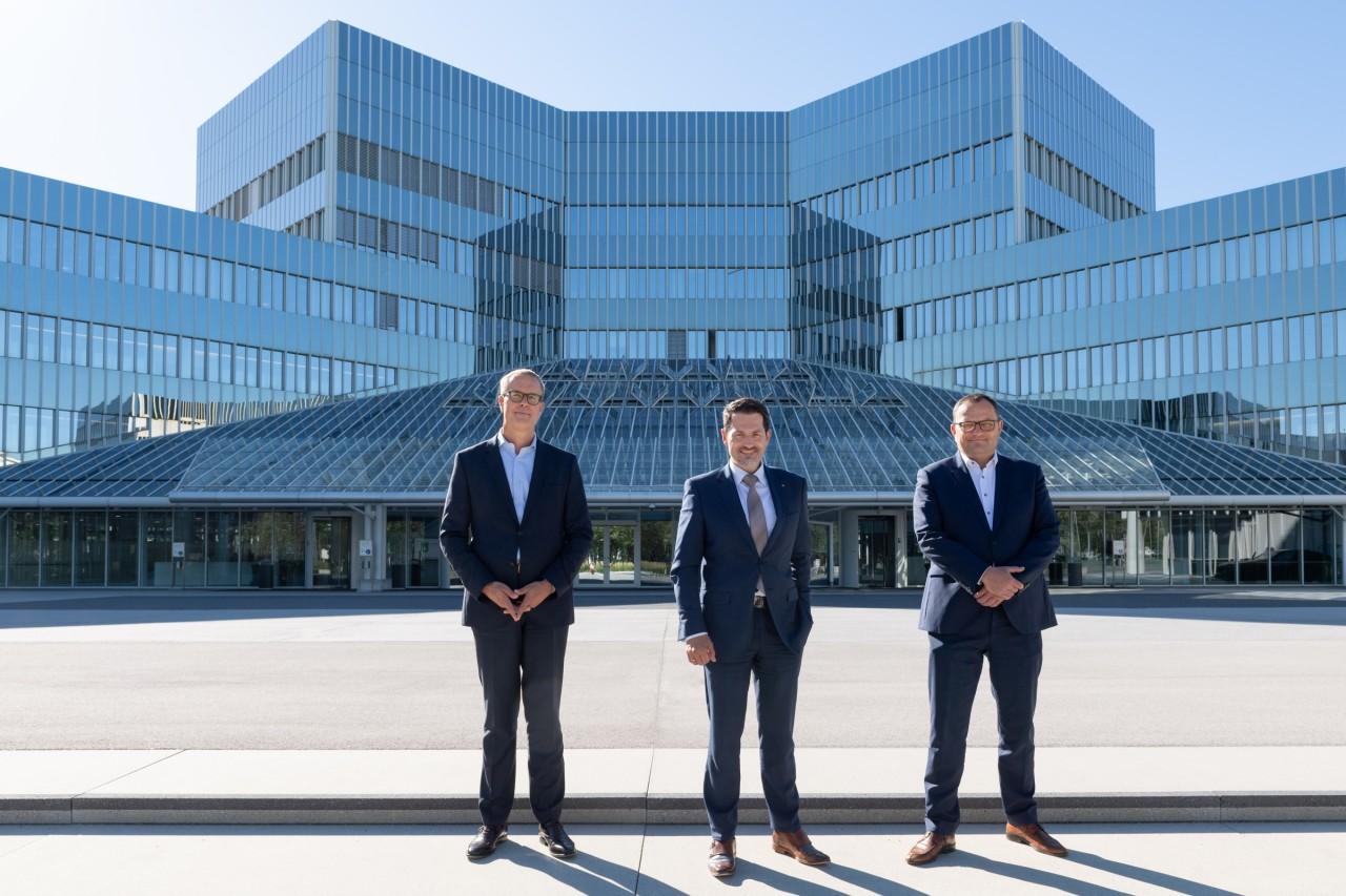Photo featuring BMW AG Board of Management member Frank Weber, TUM president Thomas F. Hofmann, BMW AG CIO Alexander Bureschin front of a big modern glass building.