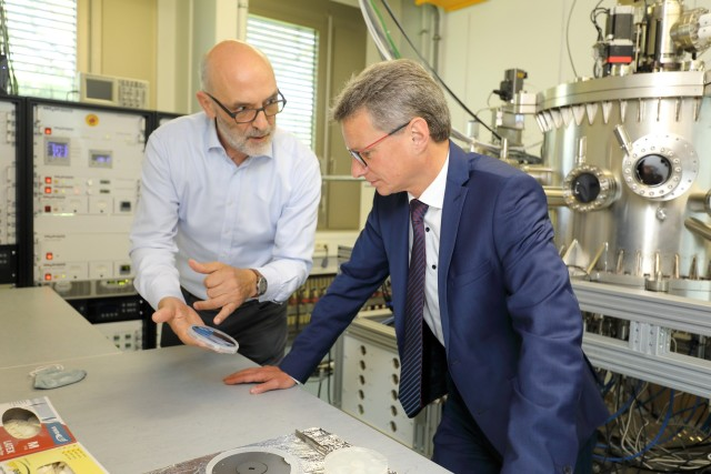 Rudolf Gross (left) of WMI shows a quantum chip to State Minister Sibler (right) in one of the WMI thin film labs.
