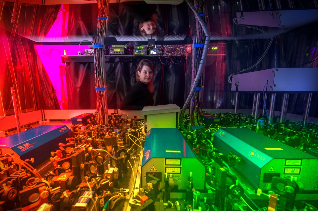 Monika Aidelsburger in one of her labs, standing behind an intricately organized assembly of lenses, mirrors, and lasers.